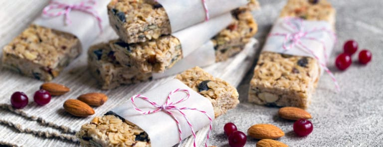 Homemade vegetarian granola bars with almonds on rustic grey background