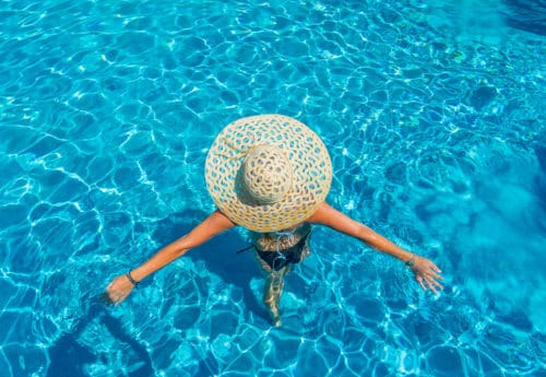 Woman at the swimming pool in a large sunhat