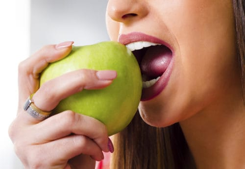 woman with perfect teeth biting green apple