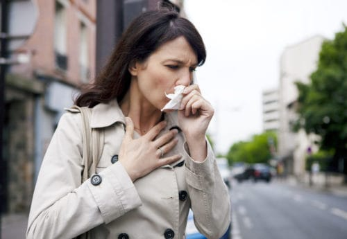 Woman wiping nose with tissue