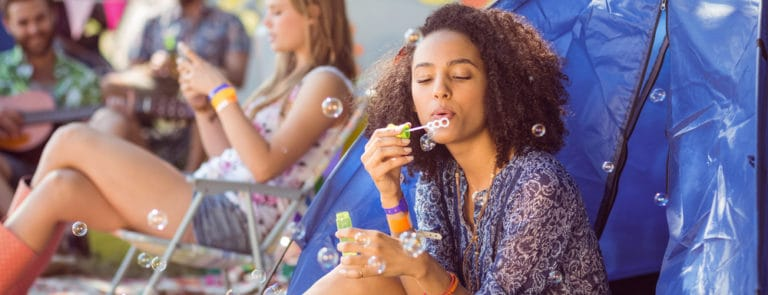 girl blowing bubbles at festival