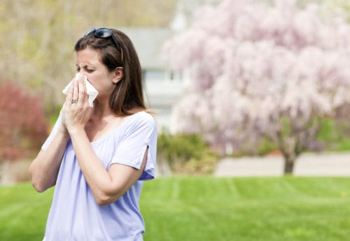 Woman outside blowing nose with a tissue