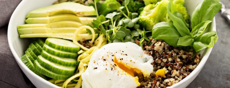 Green and healthy vegetarian grain bowl with quinoa, avocado, cucumber and poached egg