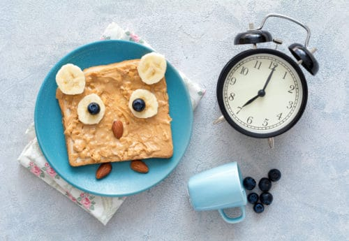 Funny owl toast with peanut butter, banana, blueberries and almonds on a blue plate, a clock and tiny cup of blueberries.
