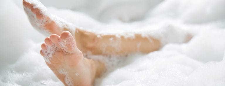 Women's feet she was bathing in a a bathtub with happiness