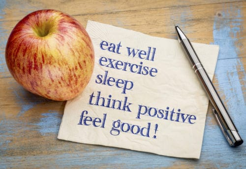 think positive , exercise, eat well, sleep - concept of feeling good - handwriting on a napkin with an apple