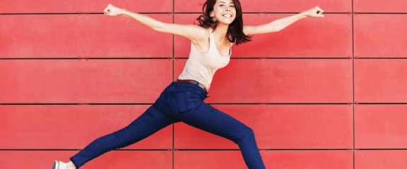 Woman jumping and smiling with arms and legs spread wide