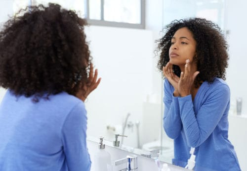 Woman looking in mirror with hands on face