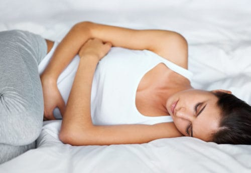 Woman lying on bed with hand on stomach