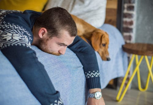 Man and dog lying on bed with sad expressions.