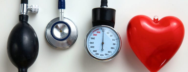 Blood pressure testing equipment next to red heart shape