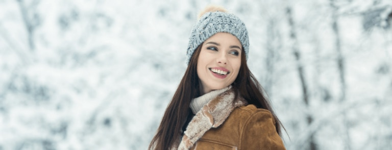 Woman outside in snow, wearing coat and hat, smiling