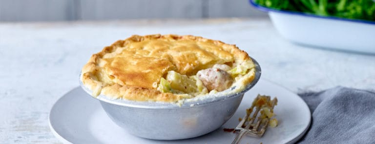 Pie with a section of the crust missing so you can see the leek, mushroom and parsnip filling