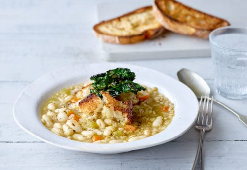 Pearl Barley Ribollita served in a white bowl topped with Crispy Cavolo Nero