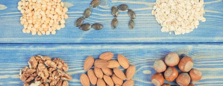 Zinc chemical symbol and piles of nuts on blue wooden background
