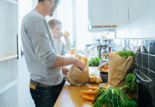 Father and toddler unpacking fruit and vegetables from shopping bags
