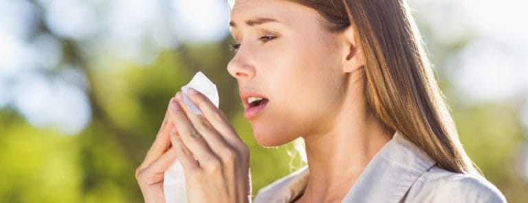 Young woman outside about to sneeze into a tissue