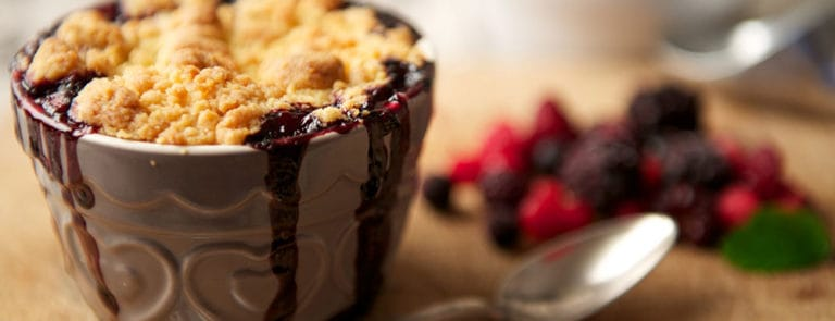 Crumble in a ceramic pot next to a handful of berries on a wooden board