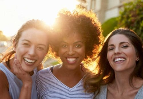 Three women with white teeth smiling at the camera with the sun behind them