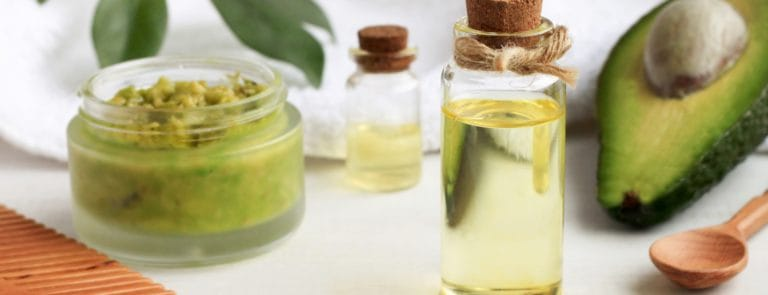 Avocado hair mask next to small bottles of oils and an avocado