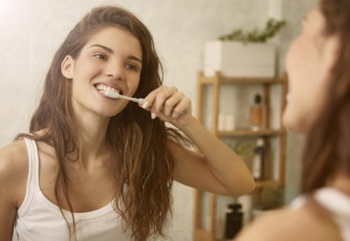 Smiling woman cleaning her teeth whilst looking in the mirror