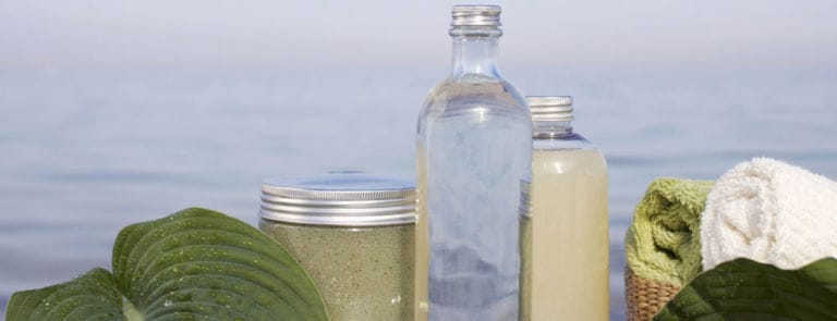 Three glass bottles and leaves on table in front of ocean.