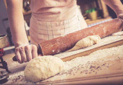 Close up of female baker hands kneading dough and making bread with a rolling pin.