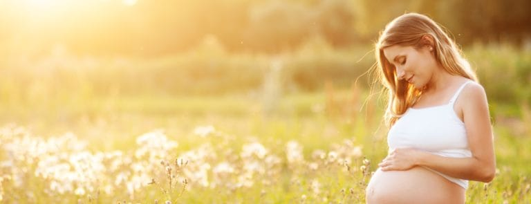 Pregnancy woman in a field with the sun shining