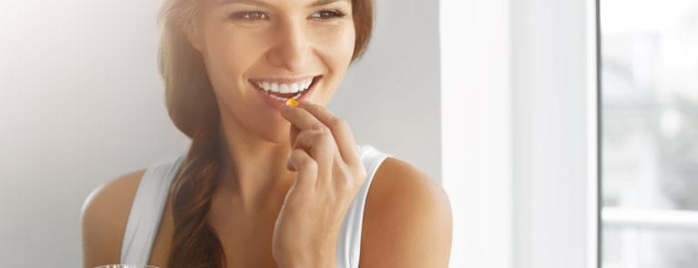 Close Up Of Happy Smiling Woman Taking Pill With Cod Liver Oil Omega-3 And Holding A Glass Of Fresh Water In Morning.