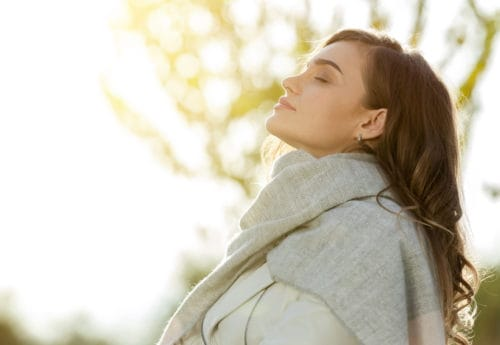 Woman outdoors wrapped in a scarf looking up into the early morning sky