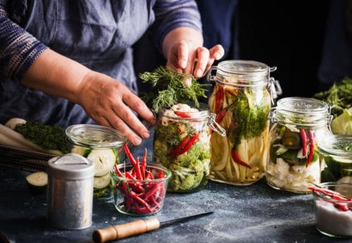 a woman fermenting foods in glass jars