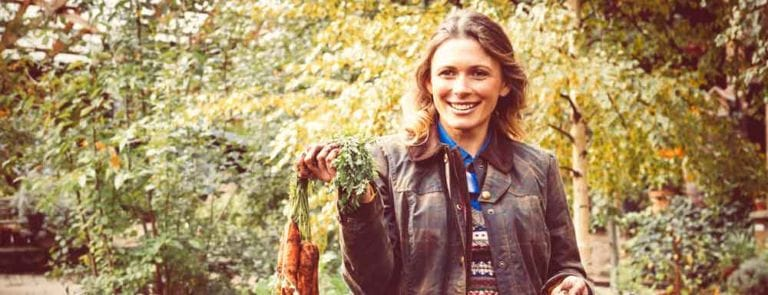 A woman holding freshly picked carrots in an allotment. Carrots are a rich source of vitamin A
