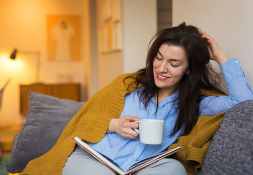 Woman reading on a sofa with a blanket and hot drink