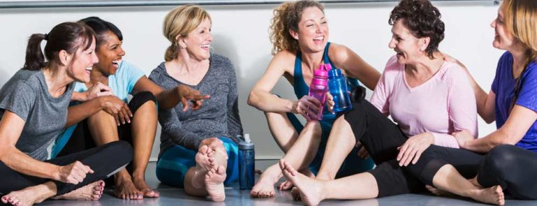 A group of women sitting down on the floor of a fitness studio in sports clothing