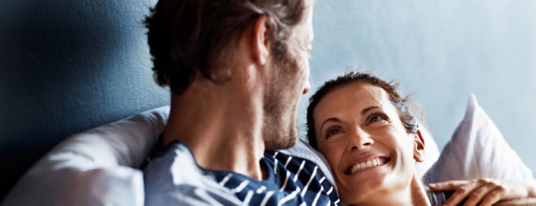 Woman smiling at her partner in bed