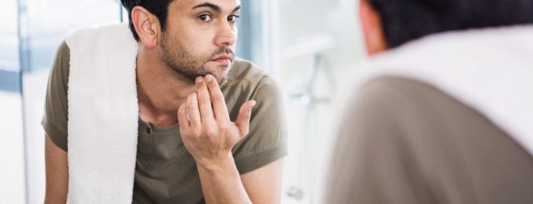 man looking into a mirror detecting if he has a cold sore