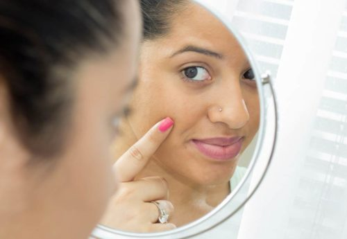 a woman looking into a mirror pointing at her face