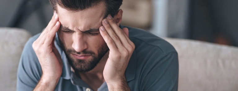 Man suffering from migraine, an ailment feverfew is used for