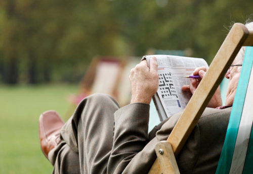 Elderly man doing crosswords, stimulating the brain which improves memory