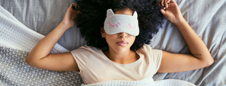 Woman wearing sleep mask, sleeping in bed