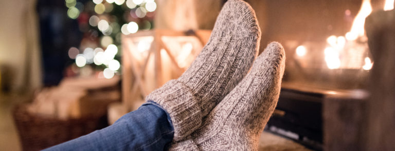 Feet up in front of a fire wearing brown woolly socks