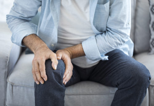 someone experiencing pain their knee due to osteoarthritis