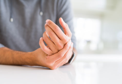types of arthritis - a man rubbing his hand as it is in pain caused by a type of arthritis
