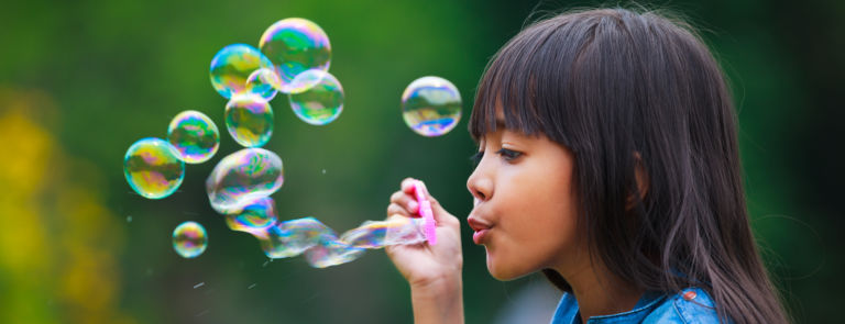 a child relaxing by blowing bubbles