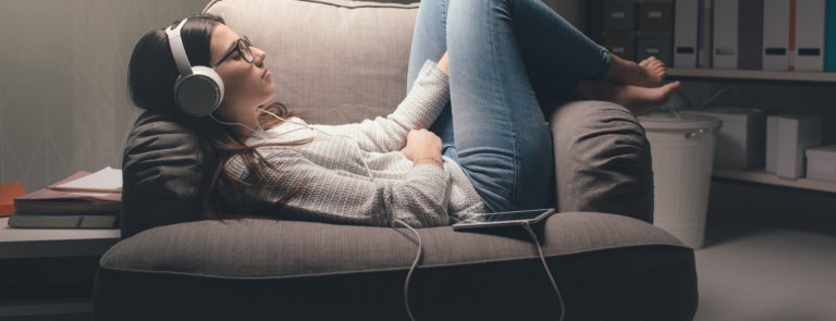 woman relaxing listening to podcast