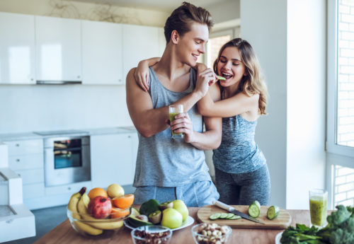 sporty couple preparing a healthy meal after their workout