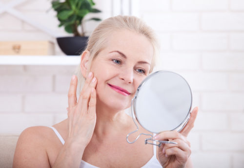 woman looking at her skin after using collagen cream