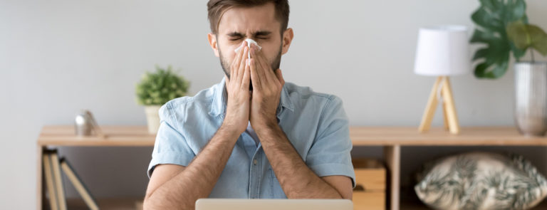 man sneezing a sign of hay fever