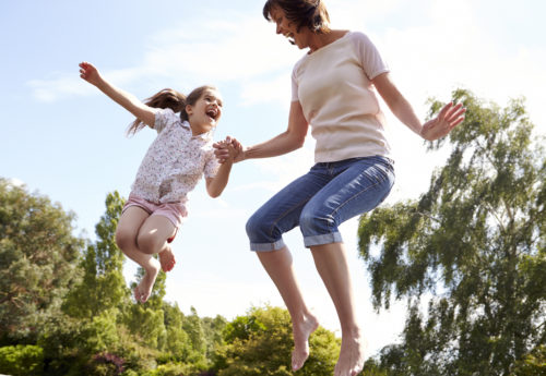 mother with daughter jumping on a trampoline filled with energy