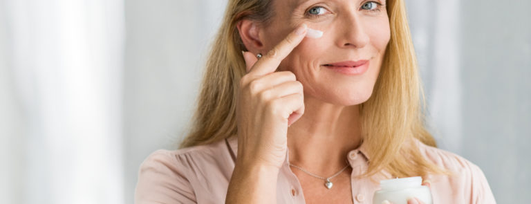 woman applying ageless beauty products to her face